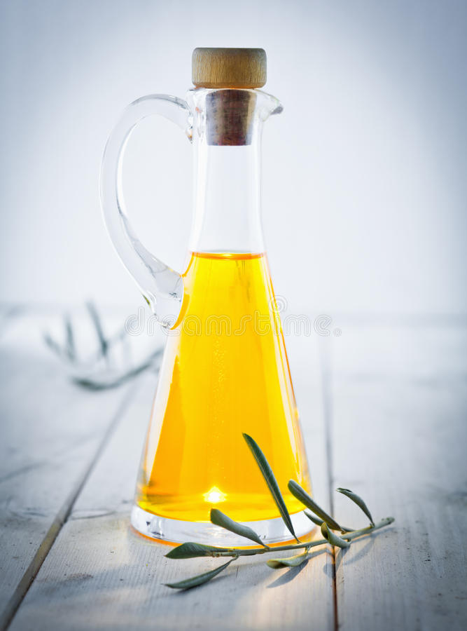 Olive Oil Carafe. With herbs and a vignette, standing on a wooden white plate, for italian kitchen royalty free stock photos
