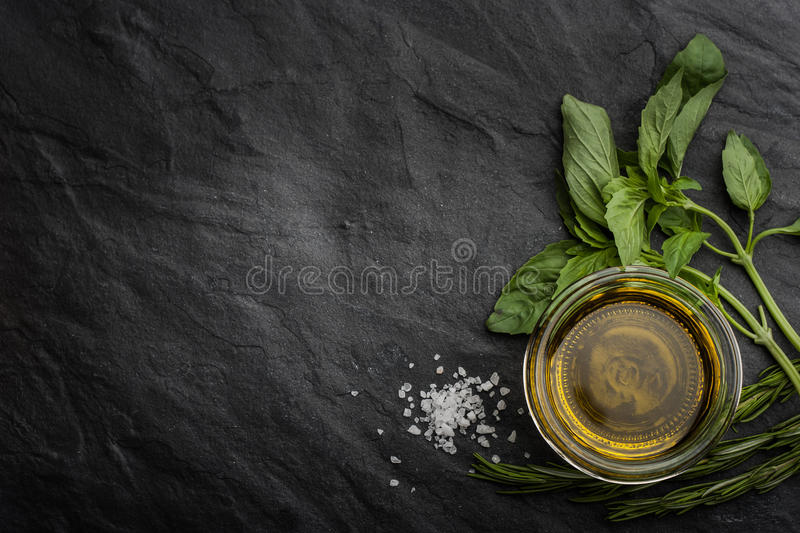 Olive oil with different greens on the right side of the black stone table stock photography