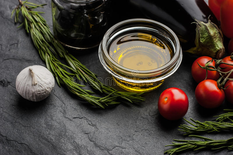Olive oil with different vegetables and rosemary on the black stone table stock image