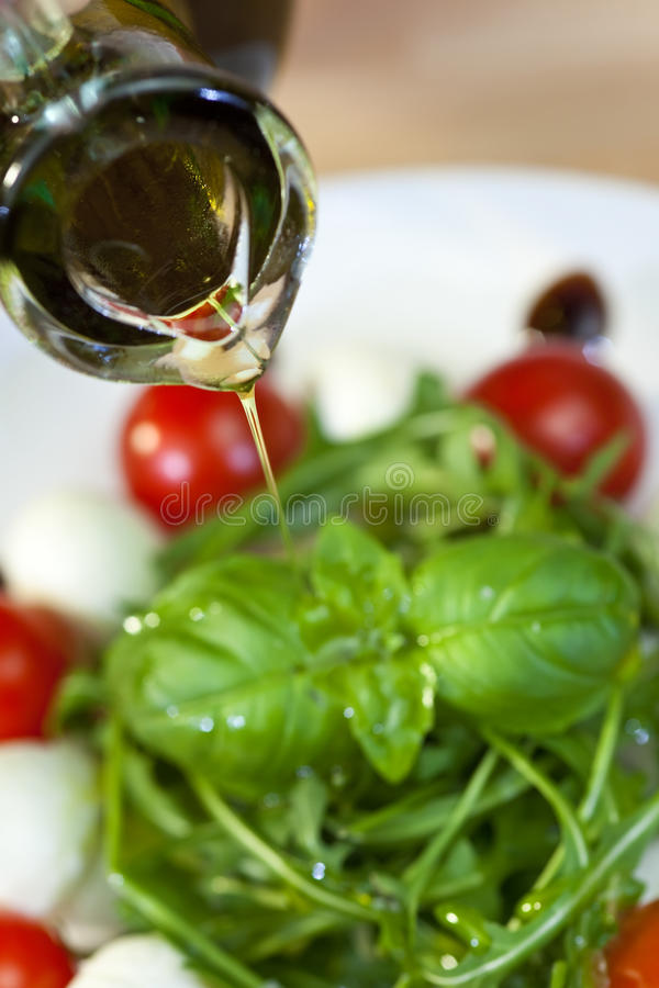 Olive Oil Dressing Pouring Onto Fresh Salad. Close up macro photograph of olive oil dressing being poured onto a fresh rocket and basil salad with cherry royalty free stock image