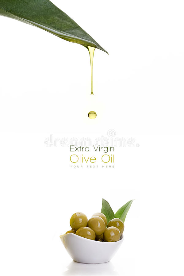 Olive oil dripping from a fresh green leaf. Olive seeds royalty free stock image