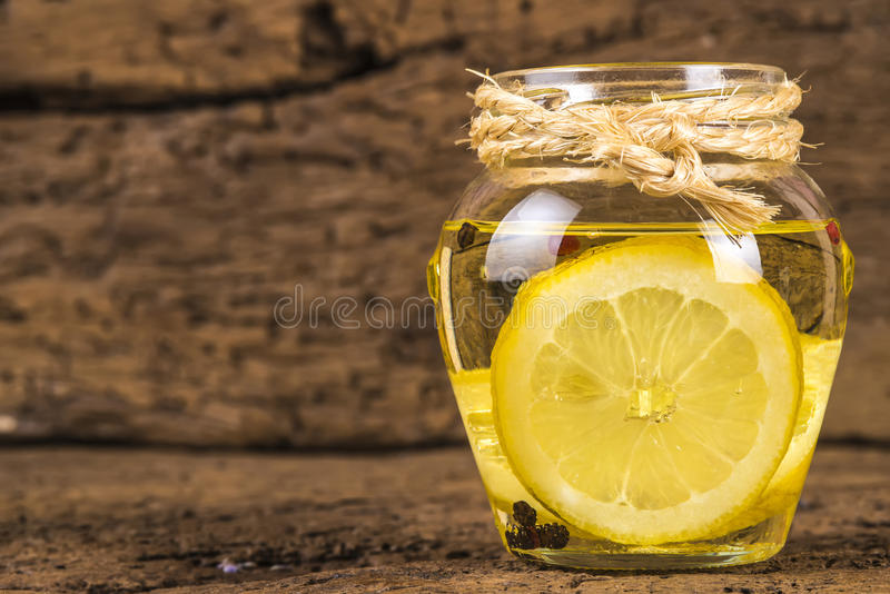 Olive oil flavored with lemon. And red beans and black pepper in a glass jar on old wooden background royalty free stock photo