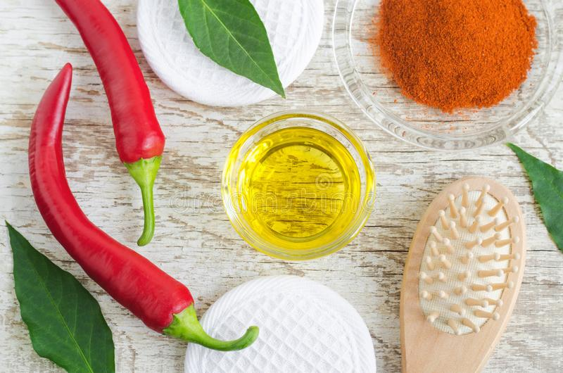 Olive oil, fresh red chili peppers and dry chili powder for preparing diy hair mask against hair loss. Baldness, alopecia remedy. Ingredients of homemade stock photo
