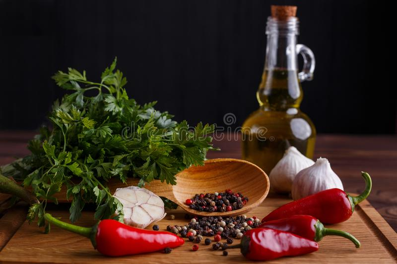 Olive oil, garlic, herbs and spices on wooden table. Kitchen bac stock image