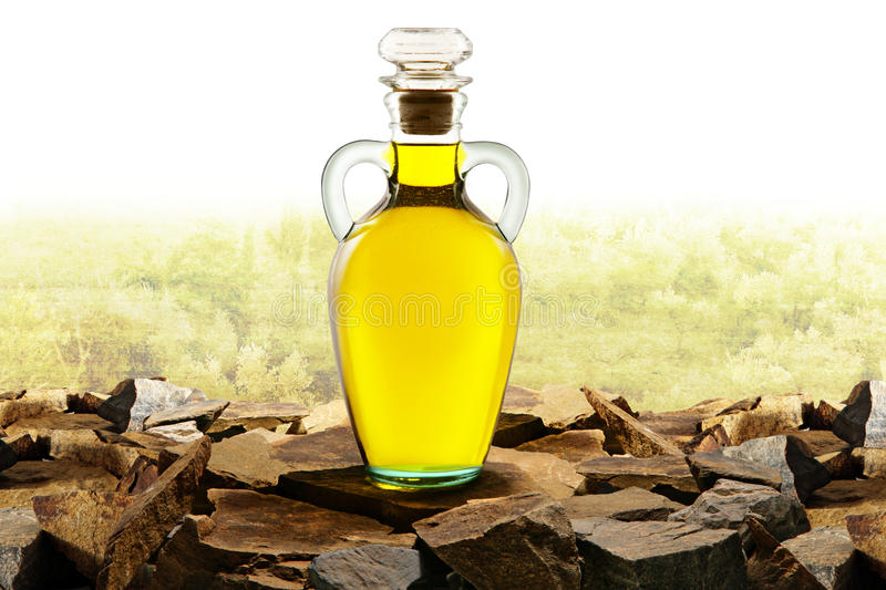 Olive oil glass bottle with olive oil. This is a photo of a olive oil glass bottle with Olive oil trees in background stock images