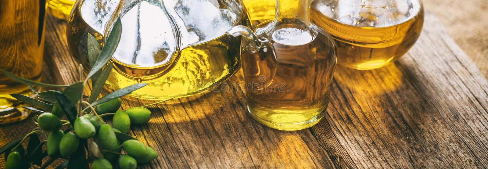 Olive oil in glass bottles on wooden table, banner, closeup view royalty free stock images
