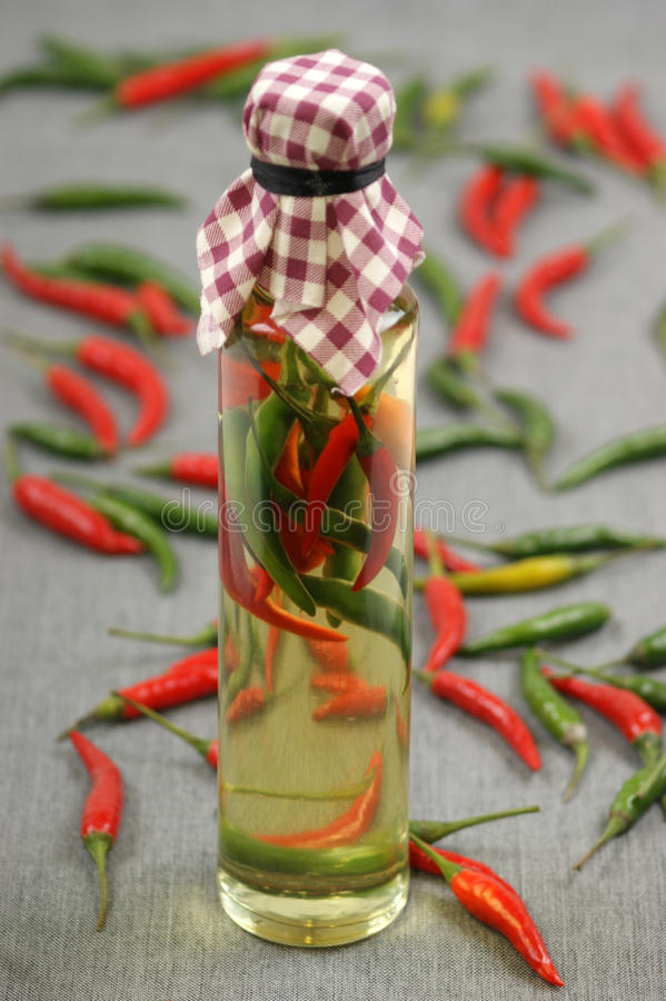 Olive oil with green and red chili stock photo