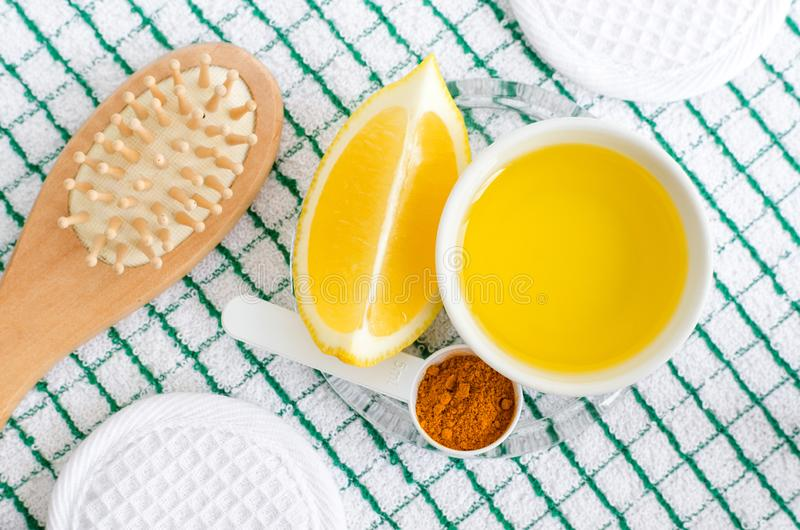 Olive oil, lemon, turmeric powder and wooden hairbrush. Ingredients for preparing diy face and hair masks and moisturizers. stock image