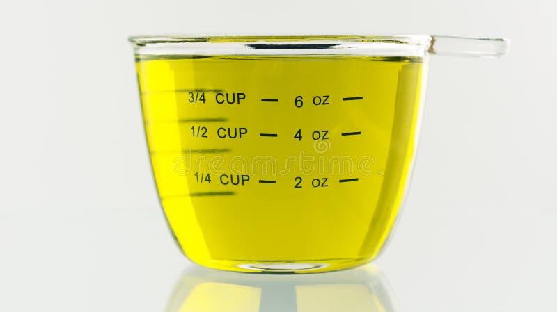 Olive Oil in 250 ml wordt gegoten die kop meten die royalty-vrije stock fotografie