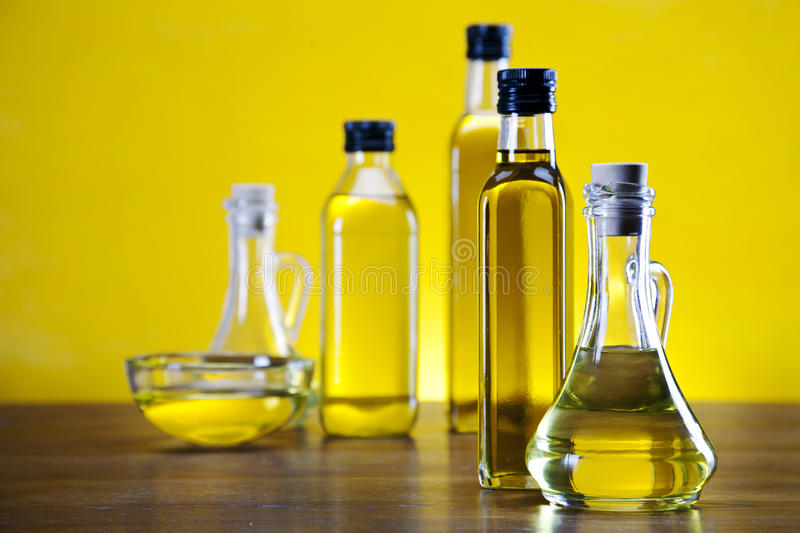 Olive oil and olives bottles on yellow background stock photos