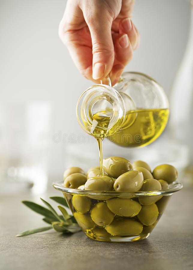 Olive oil pouring to bowl close up. Organic olive oil. Bottle of Extra virgin oil pouring in to glass bowl with olives stock photography