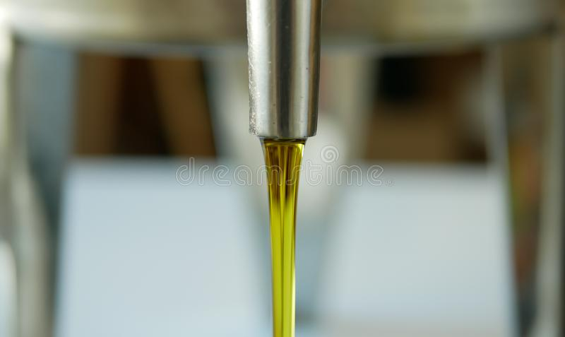 Olive oil organic quality bio, liquid obtained from olives, active, gold mixing and pouring in a steel barrel, for cold stock photo