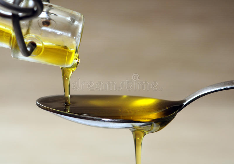 Olive oil over spoon. Extra virgin olive oil pouring from bottle to spoon closeup