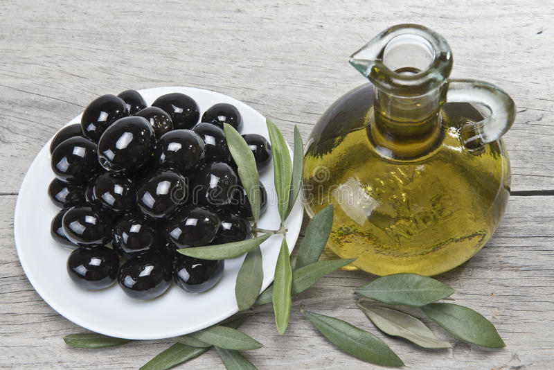 Olive oil and a plate with black olives. A jar with olive oil ans a plate with black olives on a wooden surface stock photography