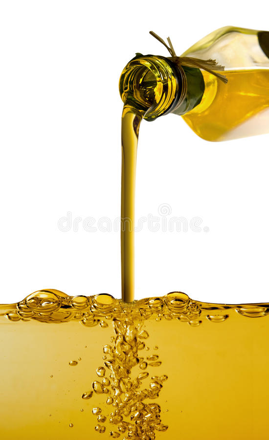 Olive oil poured from bottle. Into a container royalty free stock photo