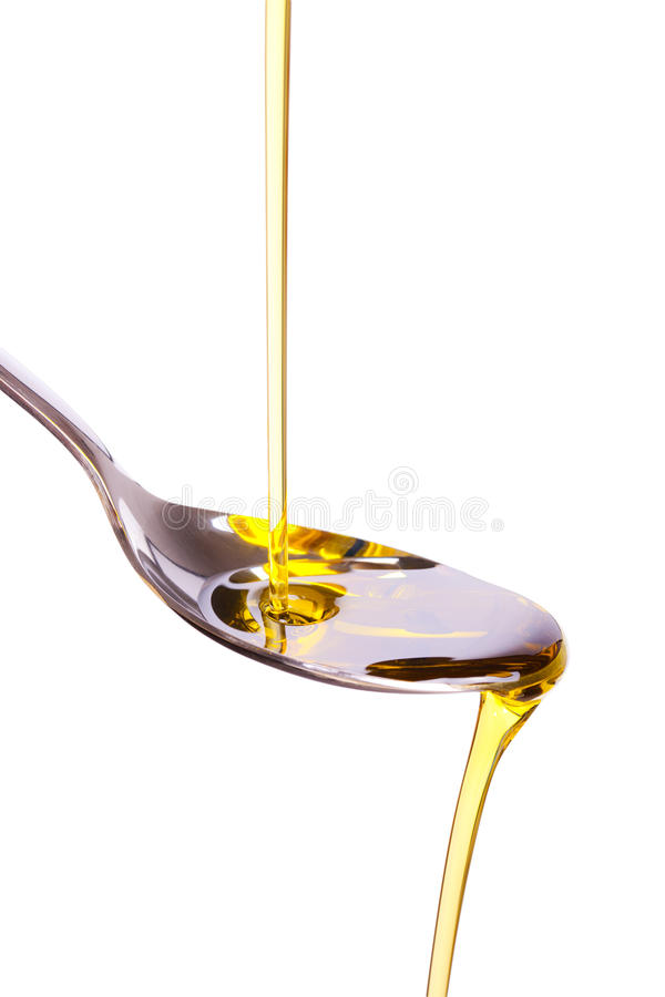 Olive oil poured into spoon royalty free stock image