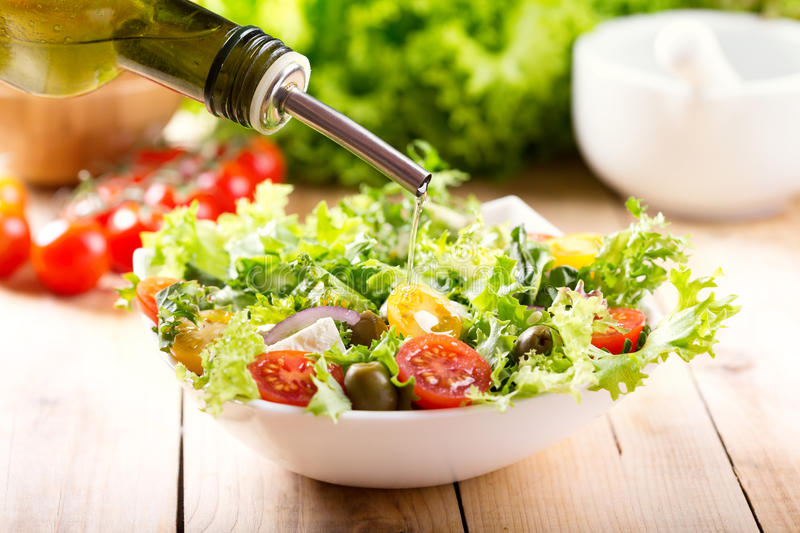 Olive oil pouring into bowl of fresh salad royalty free stock photo