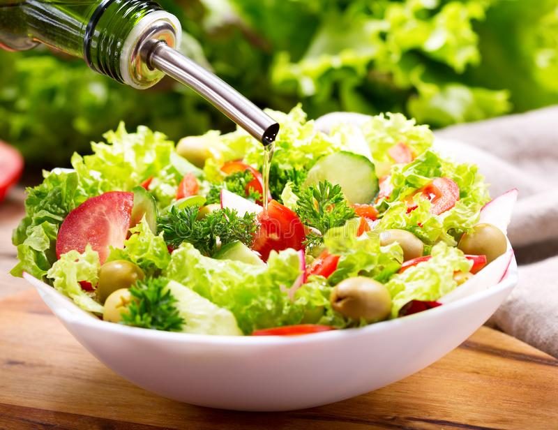 Olive oil pouring into bowl of fresh salad with vegetables royalty free stock photo