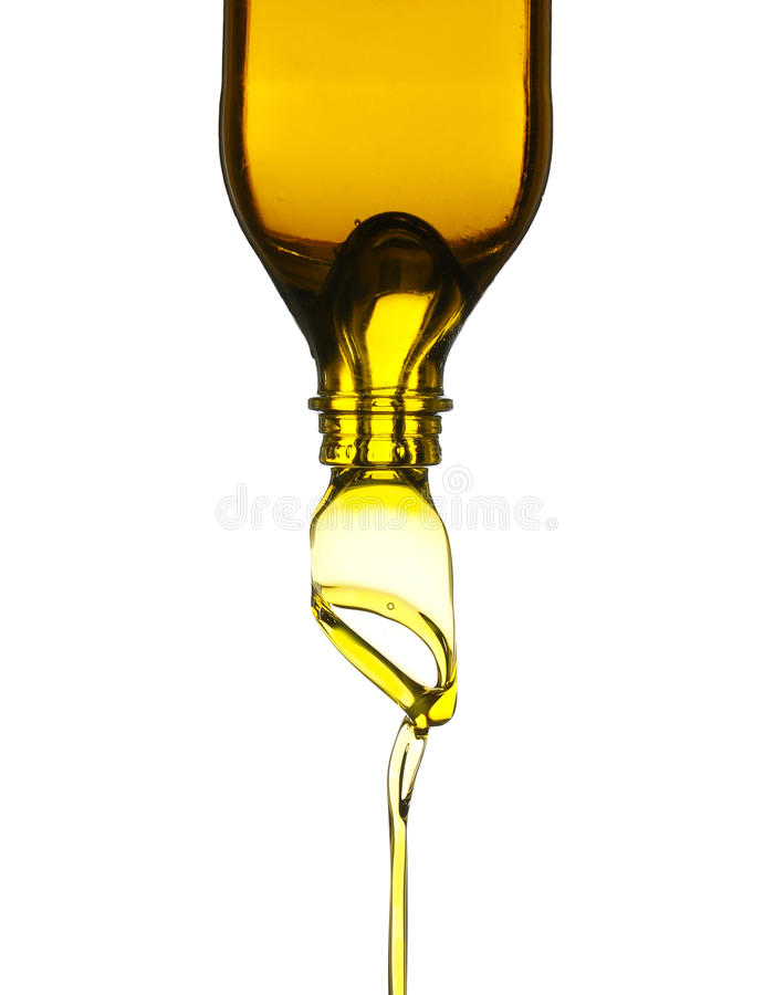 Olive oil pouring from glass bottle stock photography