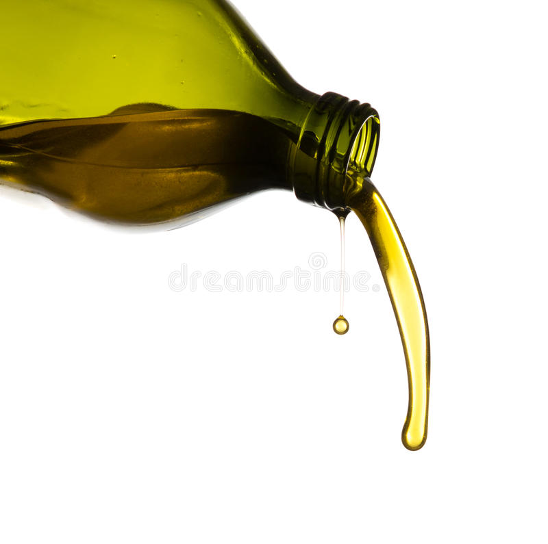Olive oil pouring from green bottle royalty free stock image