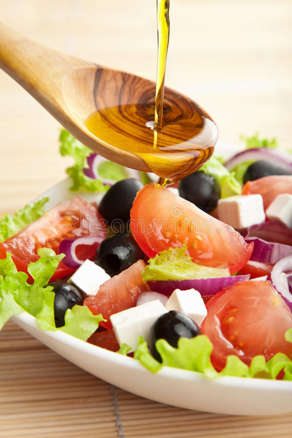 Olive oil pouring over salad stock images