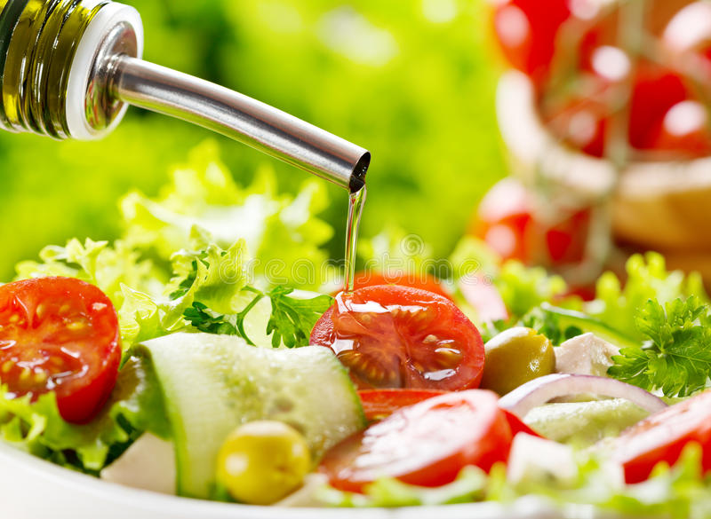 Olive oil pouring over salad royalty free stock image