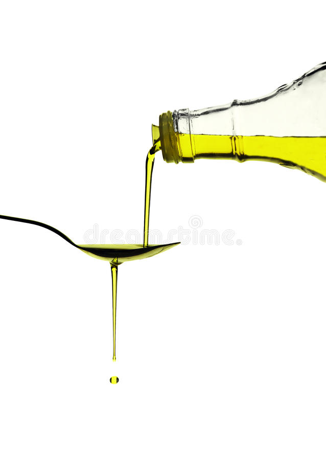 Olive Oil Pouring over a spoon royalty free stock photo