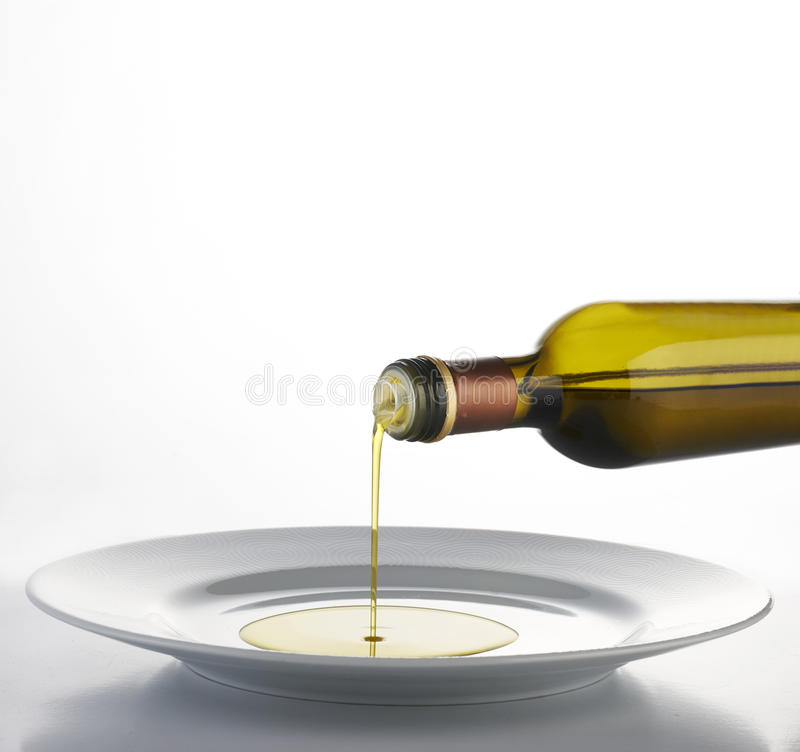 Olive oil. Pouring olive oil on a white dish stock image