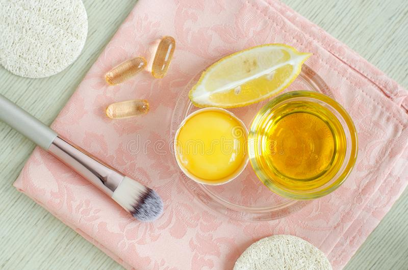 Olive oil, raw egg, lemon and vitamin E softgels - ingredients for preparing diy face and hair masks, scrubs and moisturizers. stock photos