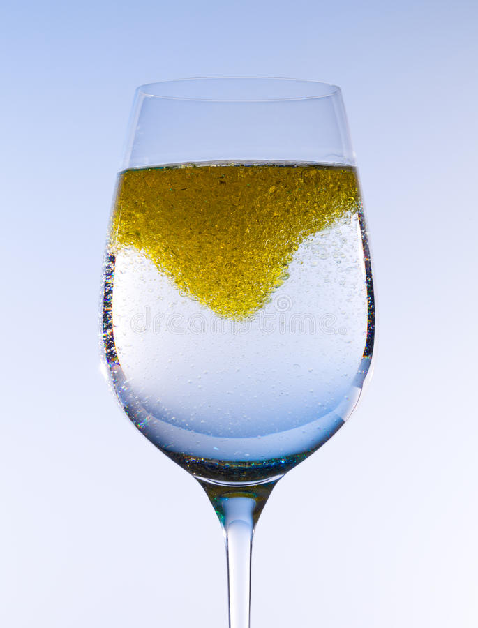Olive oil stirred into wine glass