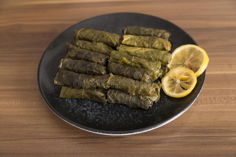 Olive oil stuffed leaves on the plate. With vegetable and lemon for service for restaurant concept from Turkey stock photography