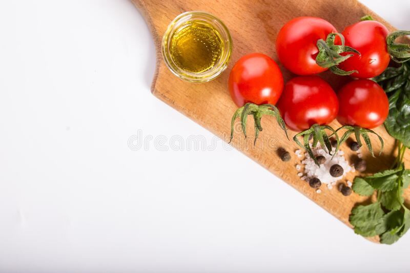 Olive oil and tomatoes. Cherry tomatoes with solt, spices olive oil on a kitchen board royalty free stock photo