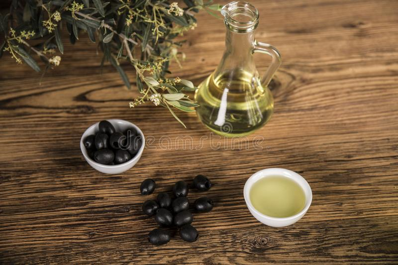 Olive oil and olive tree and black olives and bottles with olive on a wooden table.  stock photography