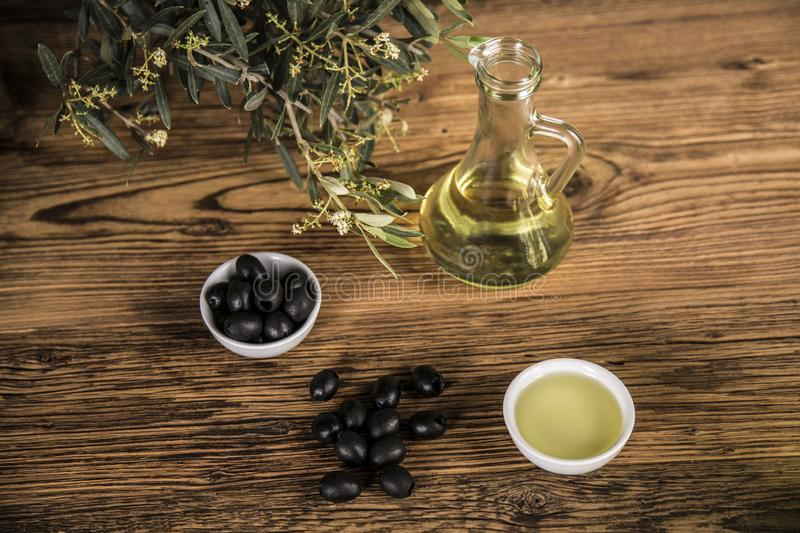 Olive oil and olive tree and black olives and bottles with olive on a wooden table.  stock photo