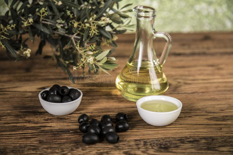 Olive oil and olive tree and black olives and bottles with olive on a wooden table.  royalty free stock photo