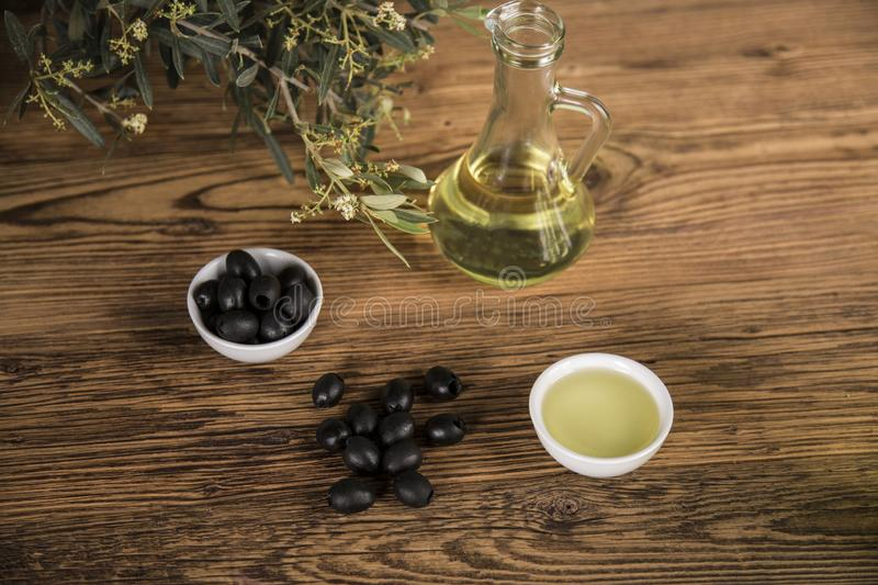Olive oil and olive tree and black olives and bottles with olive on a wooden table.  stock image