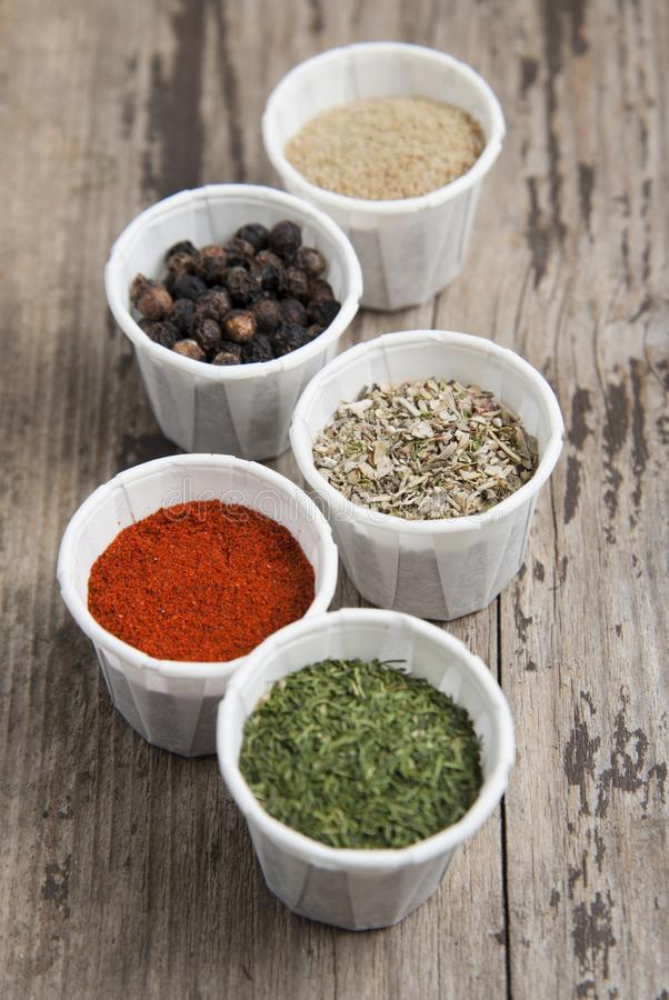 Various spices on wooden rustic background: rosemary, paprika, black pepper. Top view. Olive oil and various spices onwooden rustic background: rosemary royalty free stock photo