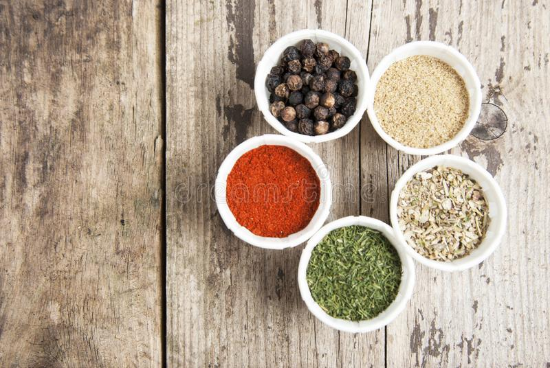 Various spices on wooden rustic background: rosemary, paprika, black pepper. Top view. Copy space. Olive oil and various spices onwooden rustic background royalty free stock photos