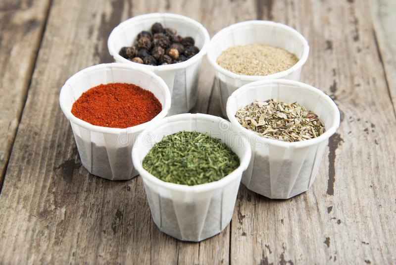 Various spices on wooden rustic background: rosemary, paprika, black pepper. Top view. Olive oil and various spices onwooden rustic background: rosemary royalty free stock image