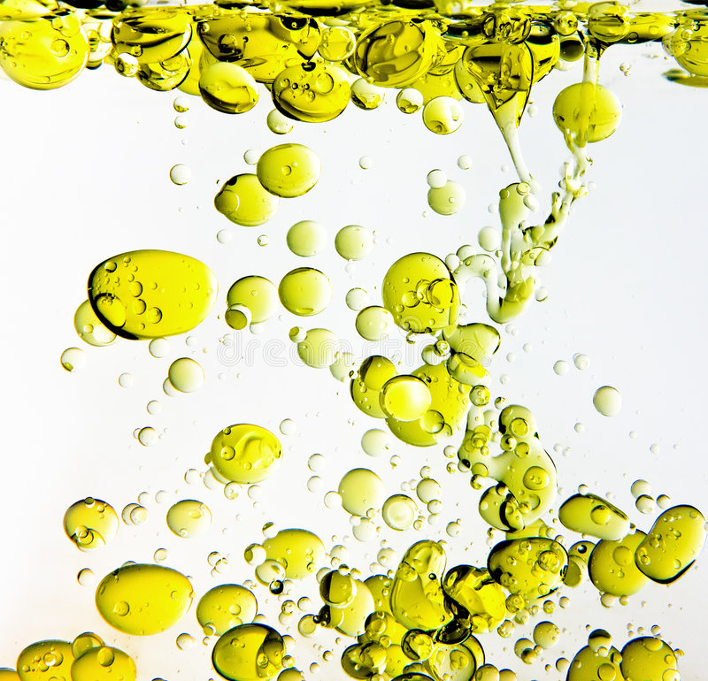 Olive Oil in Water. Olive Oil moving in shape of bubbles in water on white royalty free stock photography
