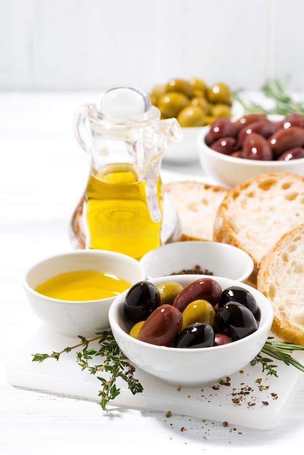 Olive, spezie e pane organici freschi su fondo bianco fotografia stock