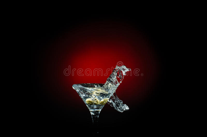 Olive splashing on cocktail isolated on red and black background royalty free stock photos