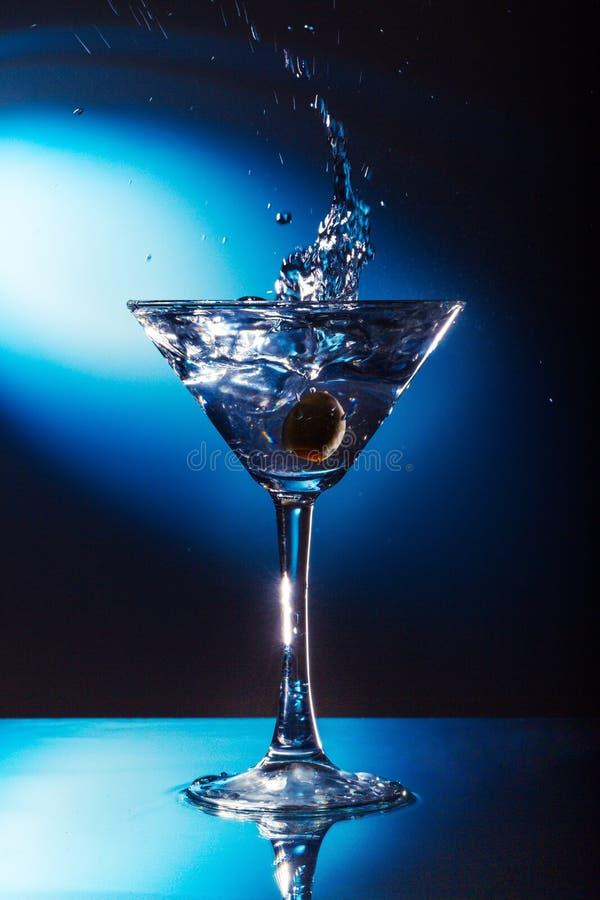 Olive Splashing em um cocktail imagens de stock royalty free