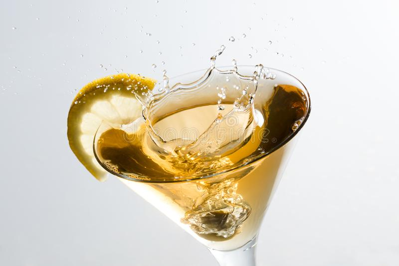 An olive splashing on a glass of martini with a slice of lemon stock photo