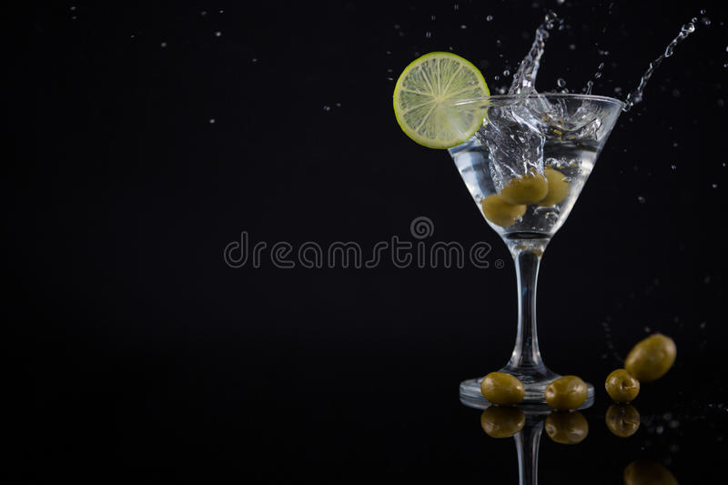 Olive splashing in to a cocktail martini with lime on table stock image