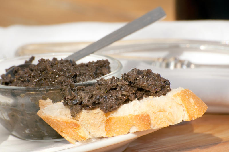 Olive tapenade. In bowl and on bread stock images