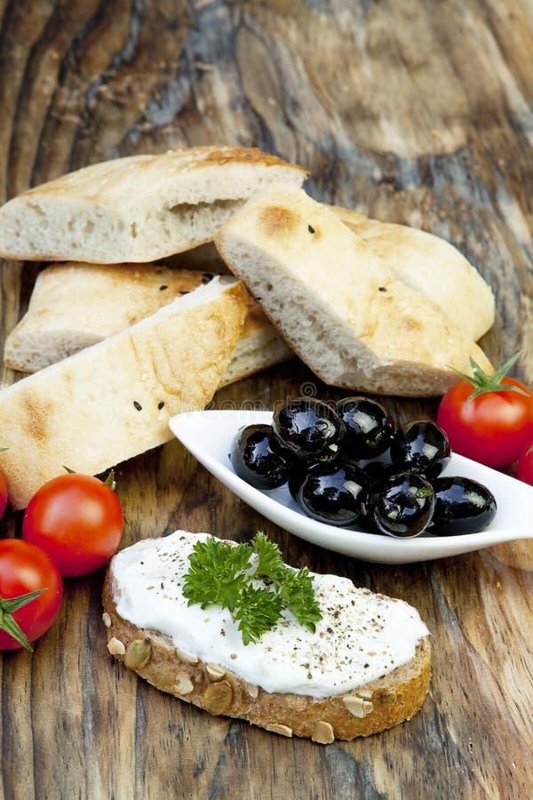 Olive verdi con pane fresco e le erbe immagini stock libere da diritti