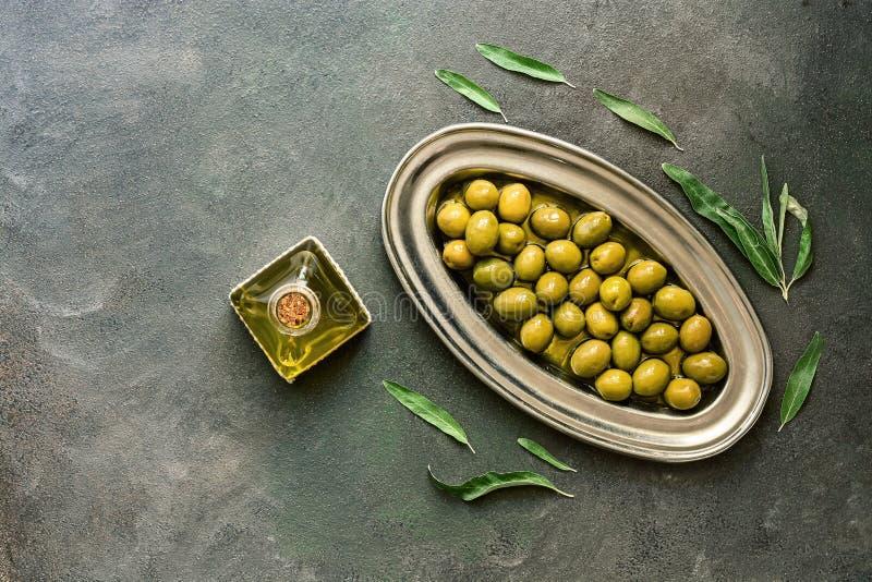 Olive verdi in olio d'oliva, fondo rustico di piastra metallica e scuro, decorato con le foglie Vista superiore, disposizione pia fotografia stock libera da diritti