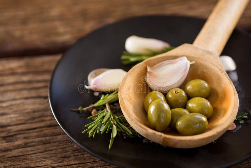 Olive verdi, rosmarini e siviera di legno sulla tavola immagine stock libera da diritti