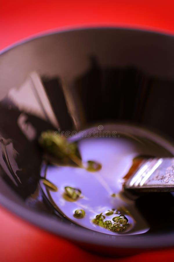 Olivenöl mit Kräutern in der schwarzen Schüssel stockbild